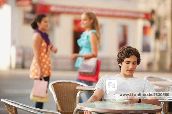 Young man waiting at cafe with friends in background