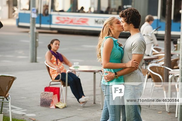 Couple kissing at cafe with woman in background