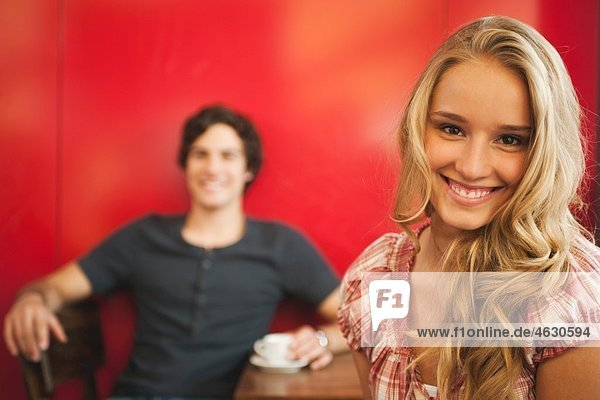 Teenage girl smiling with man in background