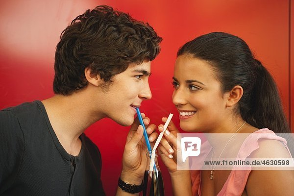 Germany  Munich  Young couple sharing a drink with straws in cafe