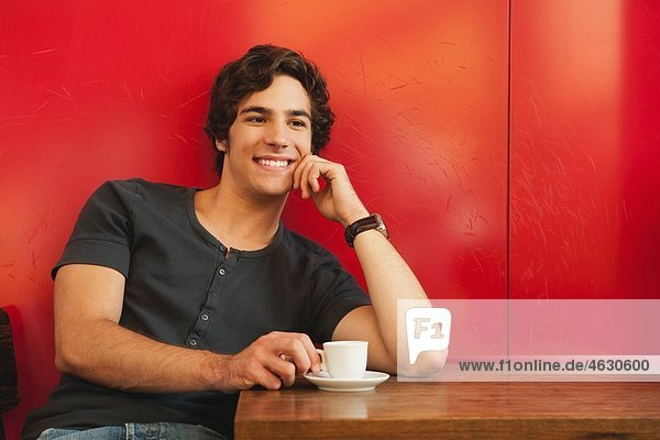 Young man in cafe  smiling