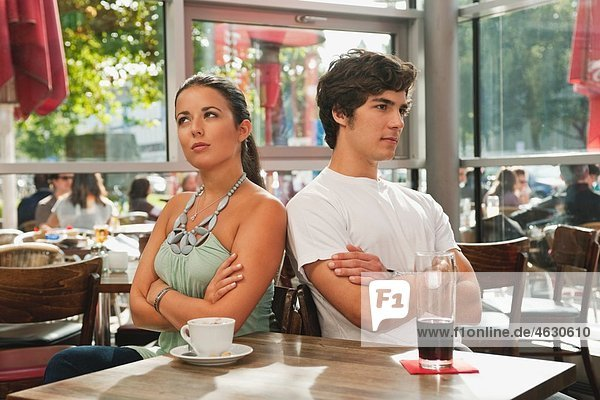Germany  Munich  Young couple looking away with arms crossed in cafe
