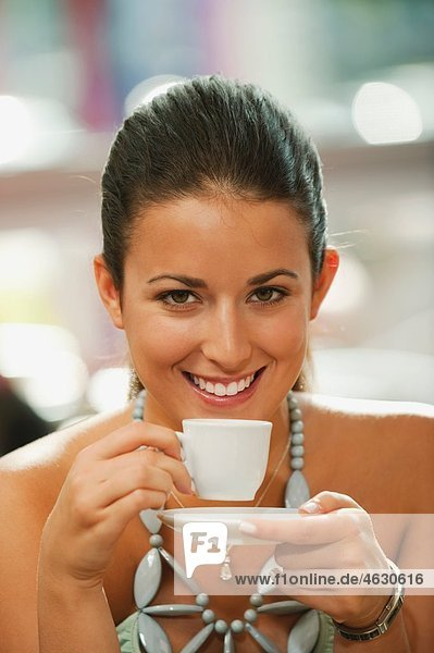 Young woman drinking coffee in cafe  smiling  portrait
