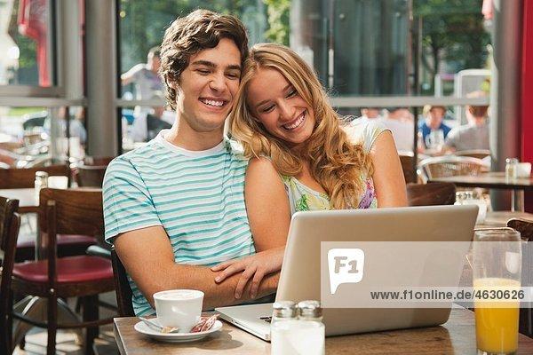 Deutschland  München  Paar mit Laptop im Cafe