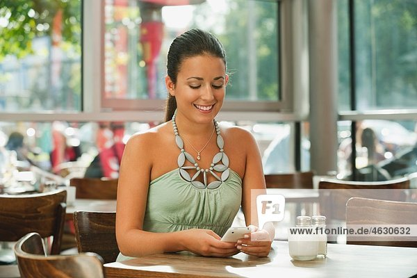 Young woman using mobile in cafe  smiling