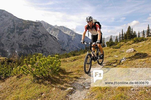 Deutschland  Bayern  Garmisch  Mountainbiker mit Bergen im Hintergrund