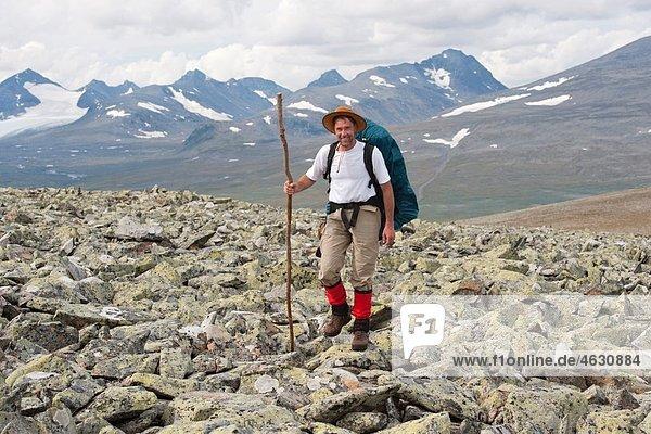Sweden  Lapland  Hiker crossing a field of rubble on the Vadvetjakka in the Sarek national park