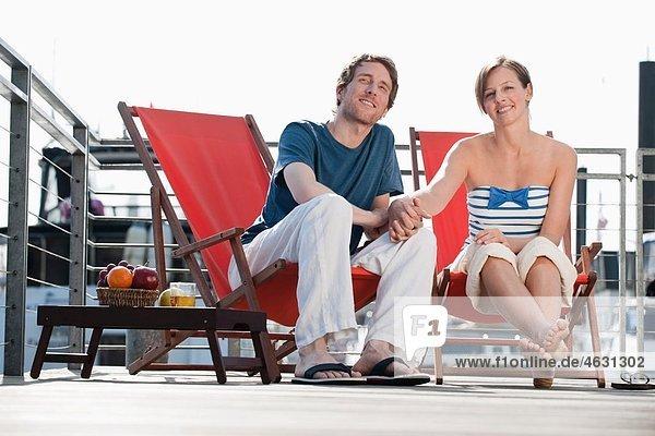 Deutschland  Hamburg  Paar im Liegestuhl schaut weg  lächelnd