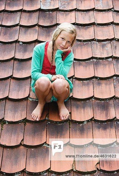 Österreich  Mondsee  Mädchen (12-13 Jahre) auf dem Dach sitzend  Portrait