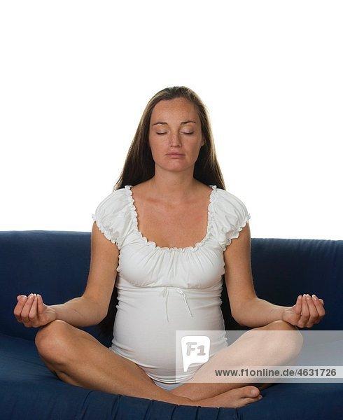 Junge schwangere Frau beim Meditieren mit geschlossenen Augen