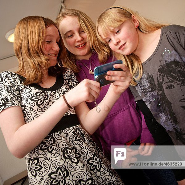 Three teenage girls reading a text message together on a mobile phone  UK