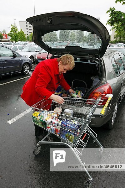 woman with a cart during shopping in a supermarket  goods will be loaded into a boot of a passenger car  D-Oberhausen  Ruhr area  Lower Rhine  North Rhine-Westphalia  D-Oberhausen-Sterkrade