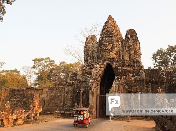 Cambodia - Tuk-tuk at the South Gate of Angkor Thom  the ¥Great Capital¥ of the Khmer empire in Angkor  with the face of Lokeshvara ¥Lord of the World¥ The temple complexes of Angkor ¥city¥ were the heart of the Khmer empire which flourished from the 9th