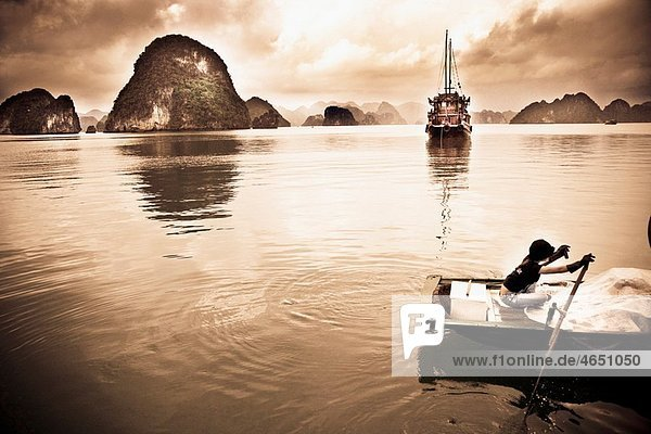 A young girl rows her boat on the waters of HALONG BAY  Vietnam