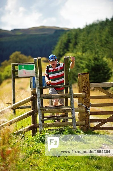 A man crossing a stile walking along the courtesy footpath on the old rail track bed  Cwm Prysor  Snowdonia National Park  Gwynedd  North Wales