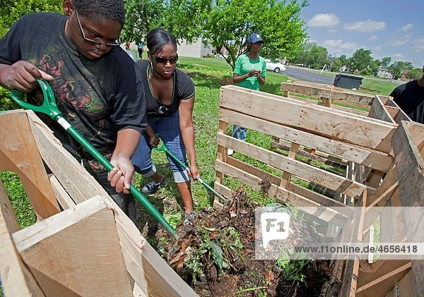 Detroit  Michigan - Students turn compost in a compost bin they have built at Genesis Lutheran Church as part of the activities at the United States Social Forum