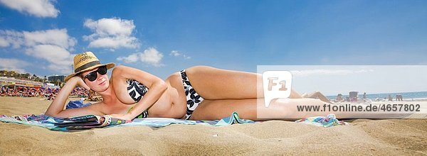Woman lying on the beach in a panoramic viewpoint
