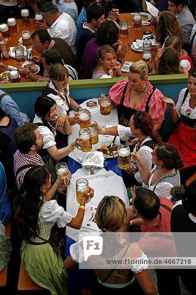 Germany Bavaria Munich Octoberfest group men and women in Bavarian costume enjoying a beer in an Oktoberfest beerhall