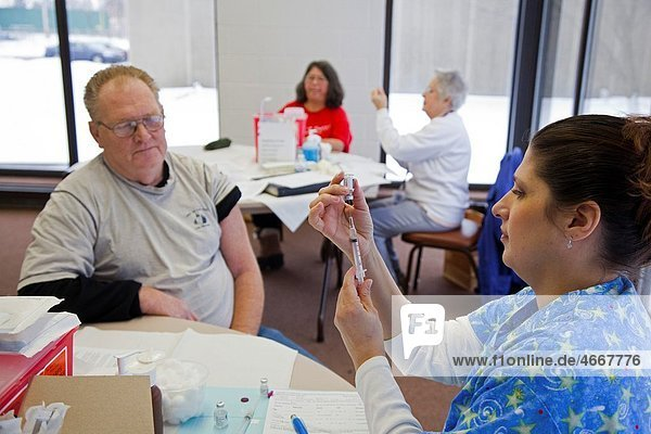 Mount Clemens  Michigan - A nurse from the Macomb County Public Health Department prepares to give an injection to a homeless man  one of a number of services provided to the homeless at the Macomb Community Center Homeless people were offered shots for