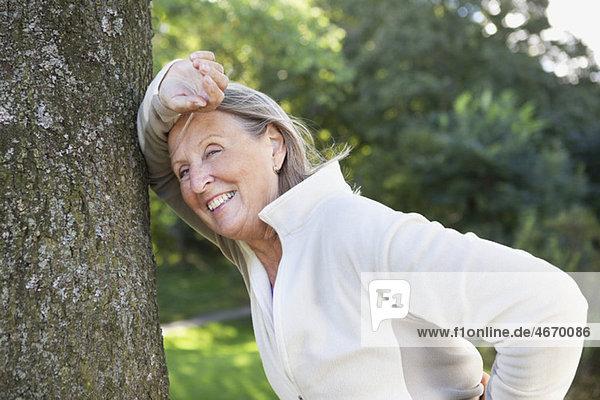 Frau an einen Baum gelehnt