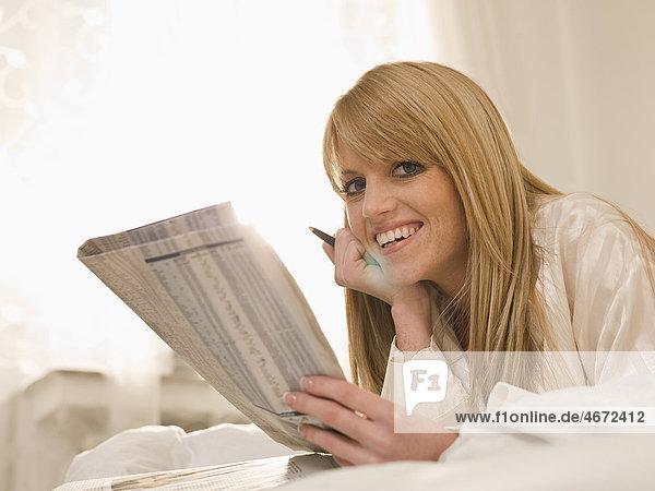 Junge Frau liegt mit Zeitung im Bett