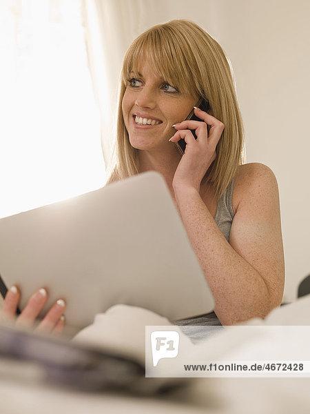 Junge Frau mit Tablet PC im Bett