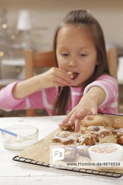 Mädchen nascht frisch gebackene Weihnachtsplätzchen
