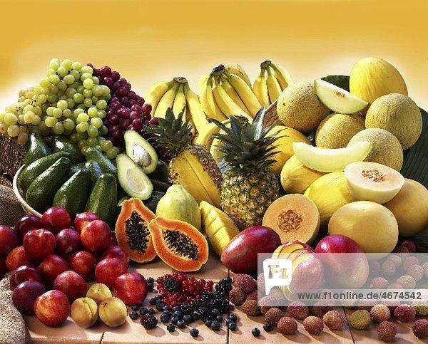 Exotisches Früchtestilleben mit Steinobst  Beeren  Avocados