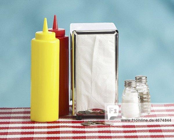 Senf- und Ketchupflasche  Serviettenspender  Salz- und Pfefferstreuer im Restaurant