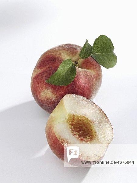 Ganzer und halber weissfleischiger Pfirsich