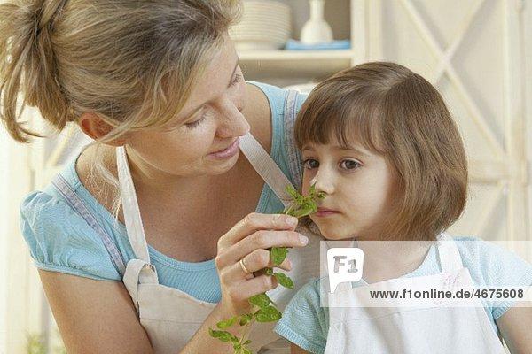 Mutter und Tochter mit frischem Basilikum
