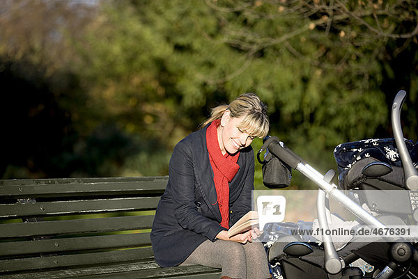 A mother sitting on a bench, reading a book LV14565054