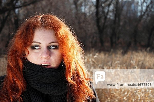 red haired girl outdoors in light of down