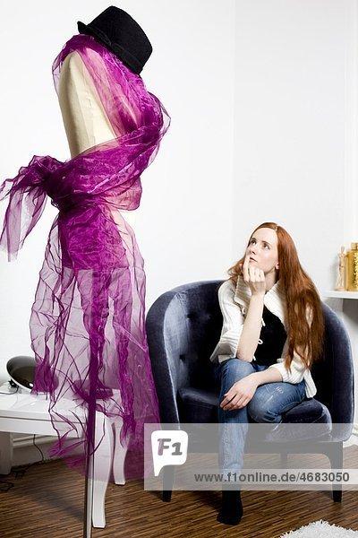 Junge Frau schaut auf Schneiderpuppe