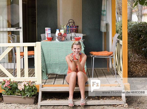 Junge Frau mit Kaffee sitzt auf einer Treppe