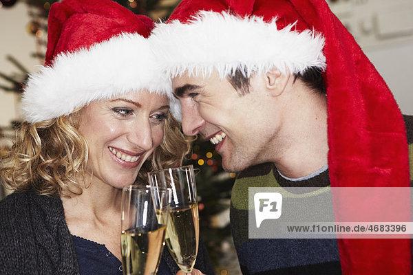 Paar mit Weihnachtskappen klirrende Gläser Paar mit Weihnachtskappen klirrende Gläser