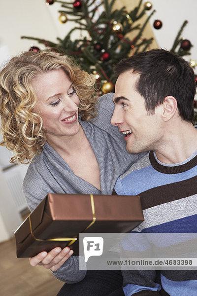 Frau überreicht dem Mann ein Geschenk Frau überreicht dem Mann ein Geschenk