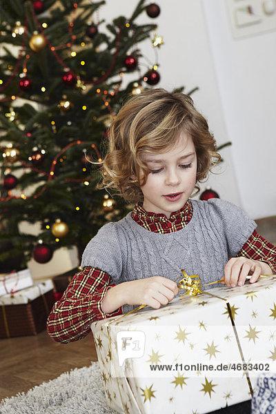 Mädchen mit großem Geschenk vor dem Baum Mädchen mit großem Geschenk vor dem Baum