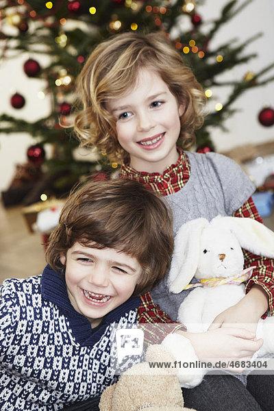 Kinder lachen vor dem Weihnachtsbaum Kinder lachen vor dem Weihnachtsbaum