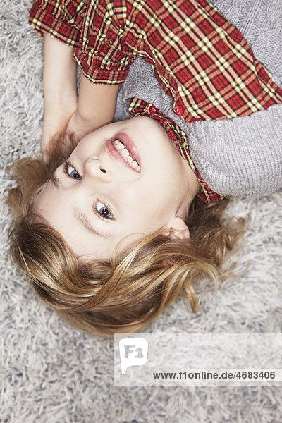 Mädchen auf Teppich liegend