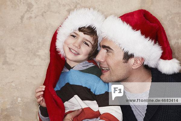 Vater und Sohn mit Weihnachtsmützen