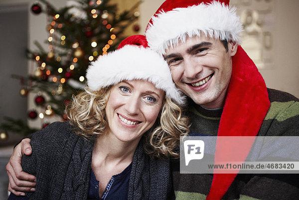 Paar mit Weihnachtsmützen vor dem Baum Paar mit Weihnachtsmützen vor dem Baum