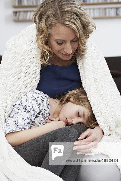 Mädchen schläft im Schoß der Mutter Mädchen schläft im Schoß der Mutter