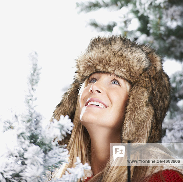 Woman with a faux-fur hat looking above