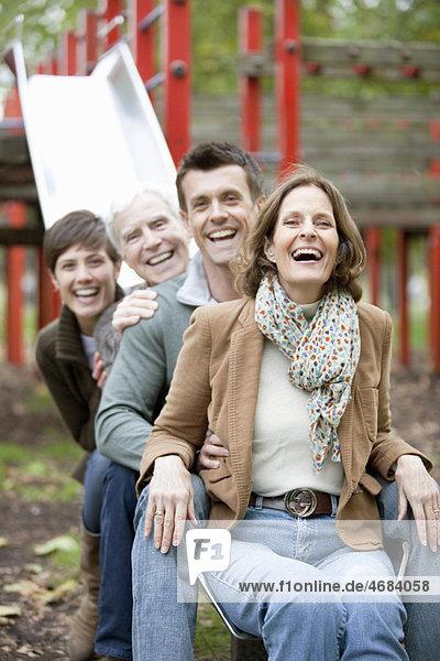 Familienportrait auf einer Rutsche im Park