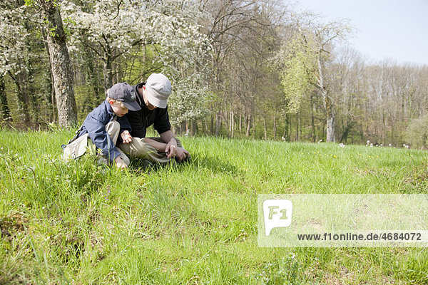 Vater und Sohn sitzen auf einem Feld.