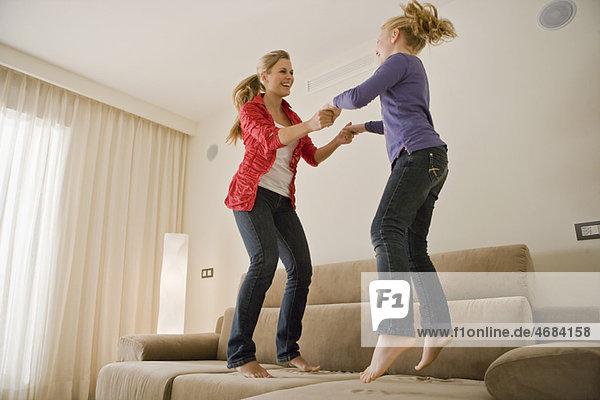 Junge Frau und Mädchen beim Springen auf dem Sofa