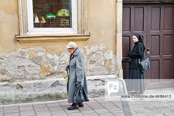 Nun looking at a woman with hat and umbrella walking in the streets of the old city of Krakow  Poland  Europe