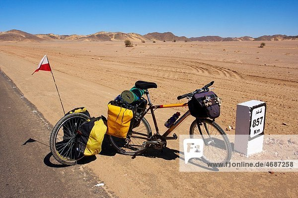 A bicycle with trailer parked by the 857 km distance bollard on the side of Sudanese road