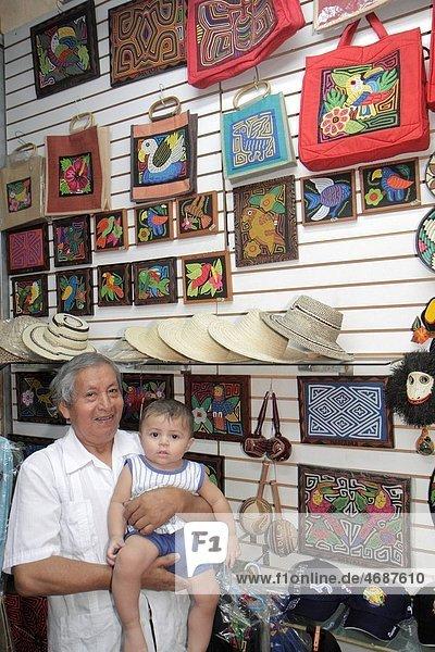 Panama  Panama City  Balboa  Centro de Artesenias  shopping  handicrafts  Kuna Indian  mola  handbag  hat souvenirs  display  indigenous heritage  embroidery  Hispanic  man  boy  baby  grandfather  grandson  child  for sale